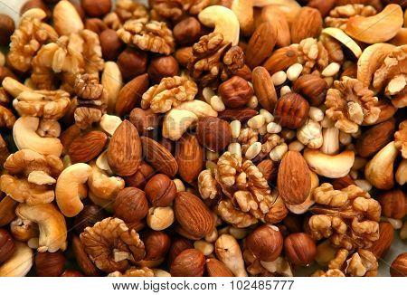 Peeled nuts in bulk as background: walnut, almonds, cashews