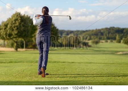 Female Golfer Striking The Golf Ball