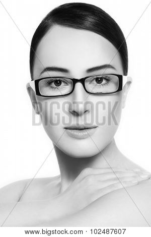 Black and white portrait of young beautiful woman in stylish glasses over white background