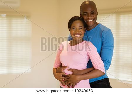 handsome african american man hugging his pretty girlfriend
