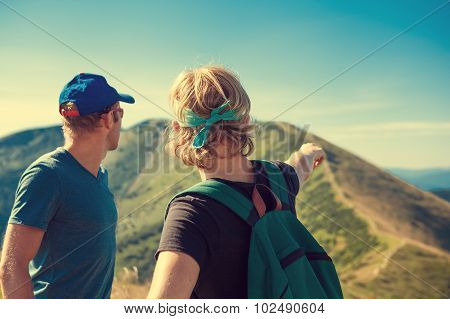 Two Travelers Discuss About Itinerary On The Top Of Mountain Hill