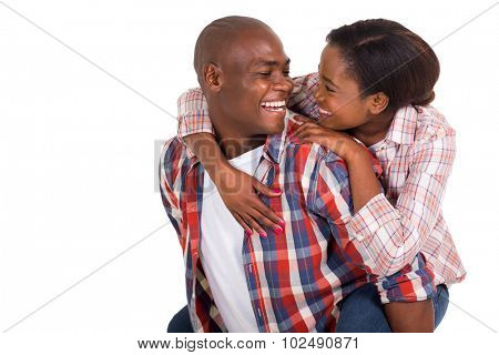 cheerful young black couple piggybacking on white background