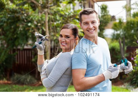 portrait of smiling young couple standing in home garden