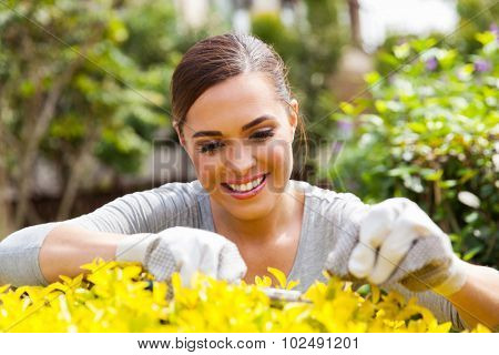smiling woman pruning plant at home garden