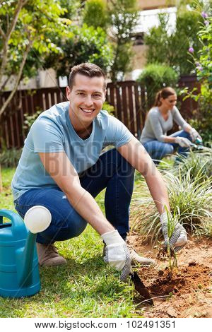 young man digging a hole before planting in home garden