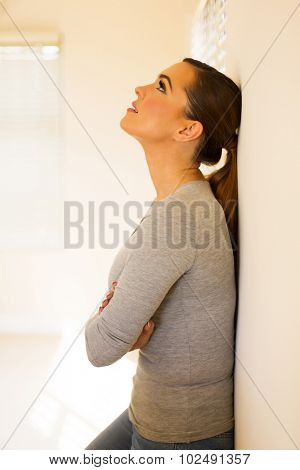 cute young woman leaning against the wall at home