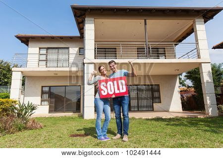 happy couple standing outside their house and holding sold sign