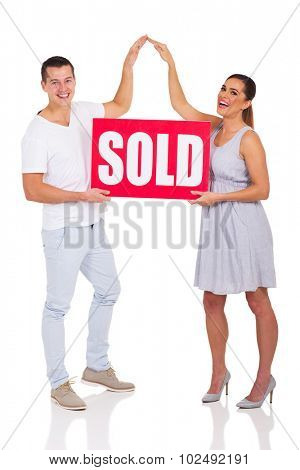 cheerful couple holding sold sign for house