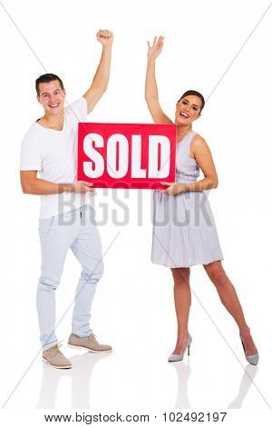 excited young couple holding sold sign isolated on white background