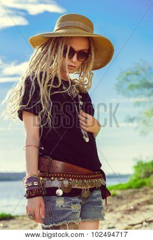 Fashion shot of a beautiful boho style girl over sky background. Boho, hippie.
