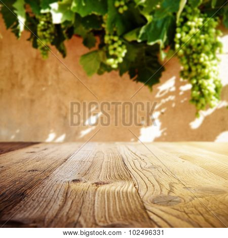 Wine background. Autumn design with vineyard and empty display. Autumn grapes harvest