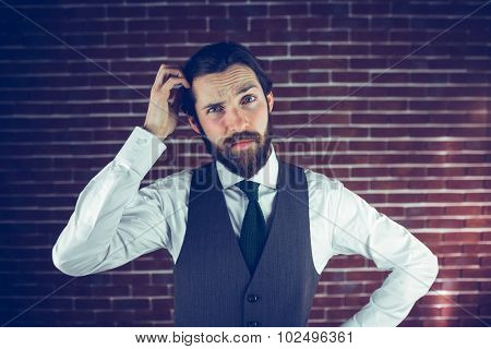 Portrait of man scratching head against brick wall