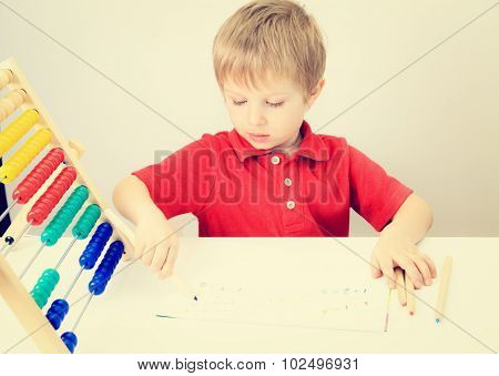 little boy learning numbers play with abacus