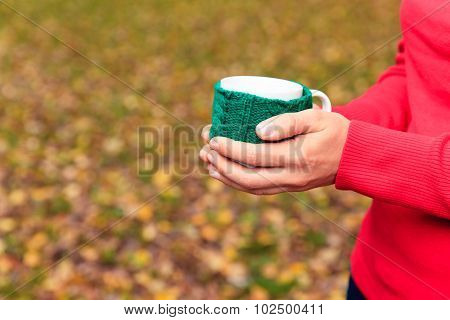 woman holding cup of tea or coffee in autumn fall