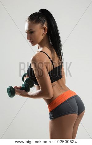 Sexy athletic woman with long hair working out with dumbbells. Sexy beautiful ass in thong.
