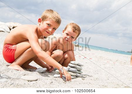 Happy Little Brothers Playing On The Beach