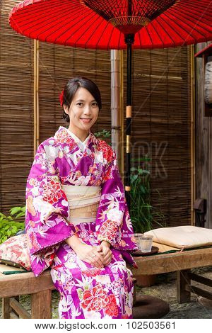 Japanese woman relaxing in tea house with kimono