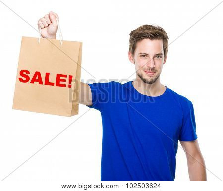 Young man hold with shopping bag and showing a word sale!