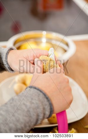 Woman Peeling Potatoes In The Kitchen