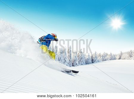 Man skier running downhill on sunny  slopes