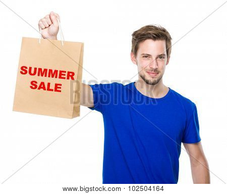 Young man hold with shopping bag and showing summer sale