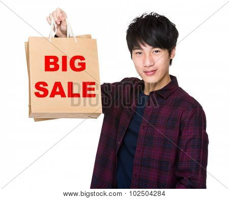 Asian Man hold with shopping bag and showing phrase of big sale