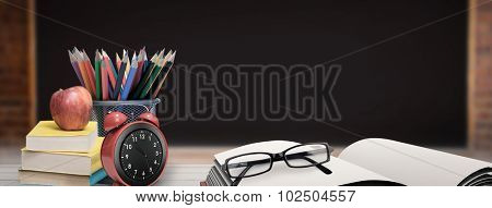 School supplies on desk against large chalkboard in classroom