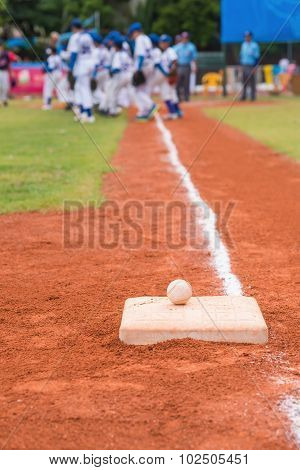 Baseball And Base On Baseball Field With Players And Judges On Background