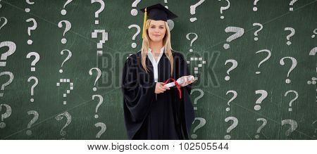 Blonde student in graduate robe holding her diploma against green chalkboard