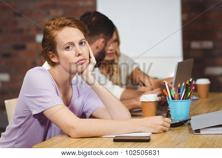 Portrait of businesswoman with hand on chin sitting in creative office