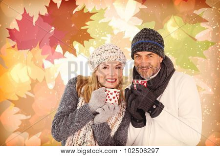 Portrait of couple drinking hot coffee against autumnal leaf pattern in warm tones