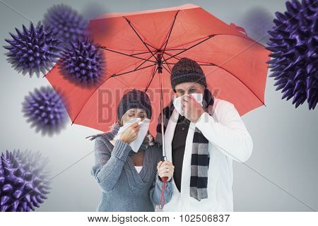 Mature couple blowing their noses under umbrella against grey vignette