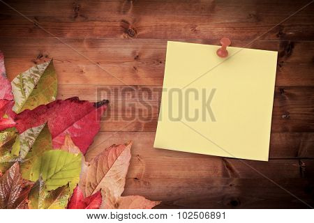 Illustrative image of pushpin on yellow paper against autumn leaves on wood