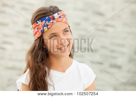 Pensive teenager girl with a flowered headband smiling outside