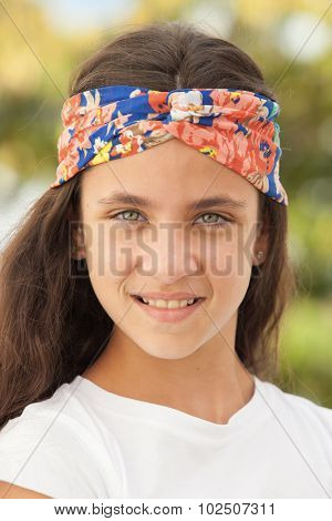 Pretty teenager girl with a flowered headband outdoor