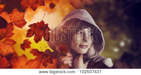 Beautiful woman wearing winter coat looking away against autumn scene