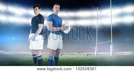 Rugby player holding rugby ball against rugby stadium
