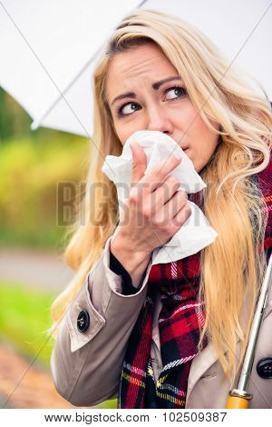 Woman having cold or flu due to bad autumn weather