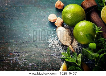 Ingredients for making mojitos (ice cubes, mint leaves, sugar and lime on rustic background)