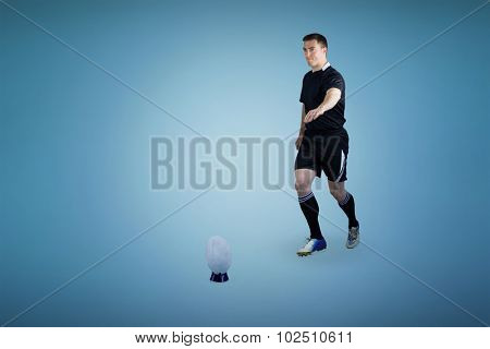 Rugby player doing a drop kick against blue background