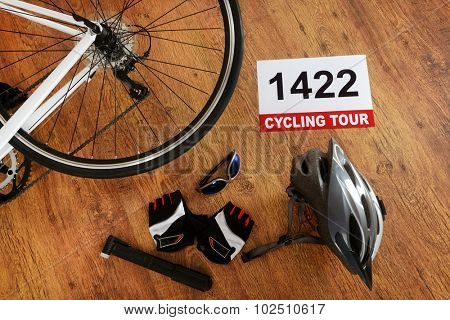 Rear bicycle wheel and other accessories on the wooden floor