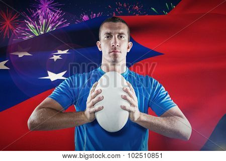 Portrait of confident sports player in blue jersey holding ball against fireworks exploding over football stadium