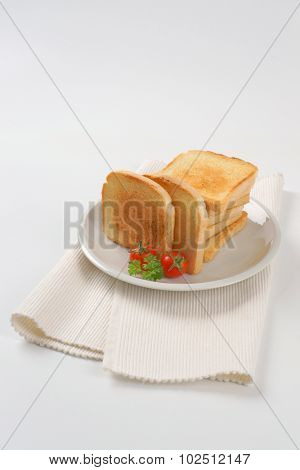 plate of freshly made toasts on white place mat