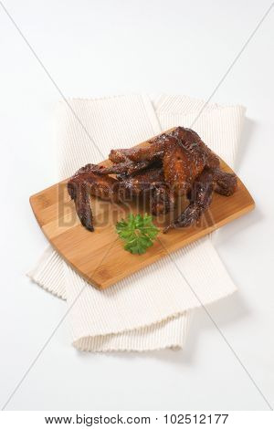 roasted chicken wings on wooden cutting board and white place mat