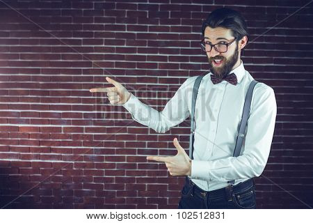 Portrait of confident hipster gesturing sideways against brick wall