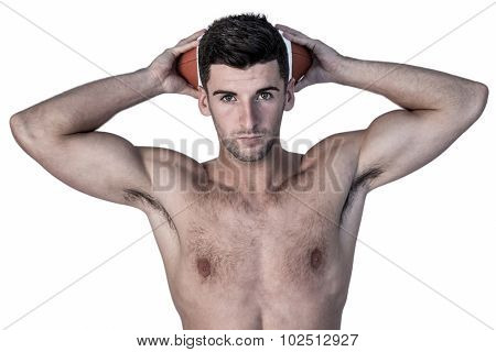 Portrait of a shirtless man holding ball over head against white background
