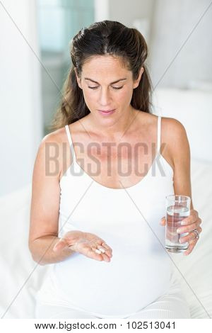 Pregnant woman sitting on bed with antibiotics and water