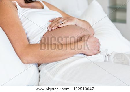 Midsection of pregnant woman reclining on bed in house