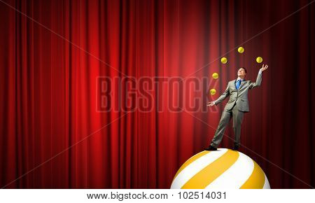 Young businessman standing on ball juggling with balls