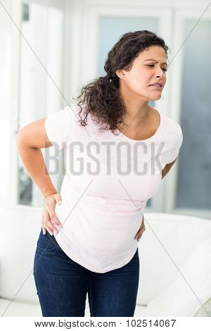 Pregnant woman frowning in back pain standing in living room